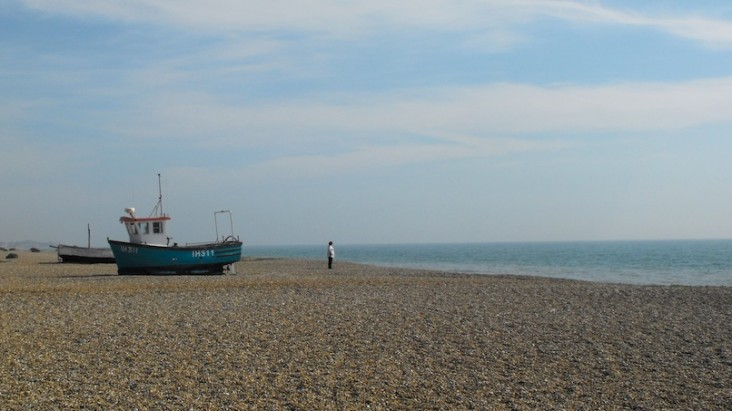 Aldeburgh beach with boat and man staring out to sea